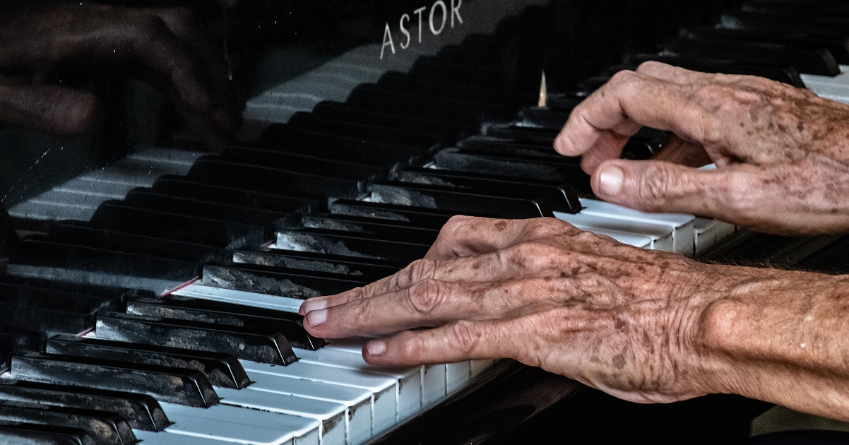 Elderly person playing piano for music article on Silver Magazine www.silvermagazine.co.uk
